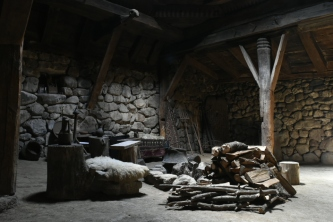 Inside stone house, mud floor, central cooking pot, no chimney.