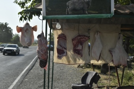 Cuts of pig hanging long the roadside
