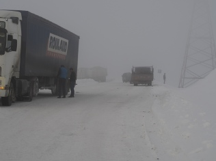 Top of the pass heading north to Osh. A lot of stuck trucks. Also many trucks not stuck. Chains seem to help.